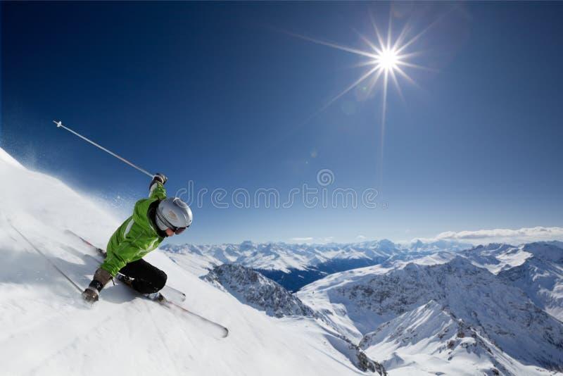 Skifahrer mit Sonne und Bergen stockfotografie