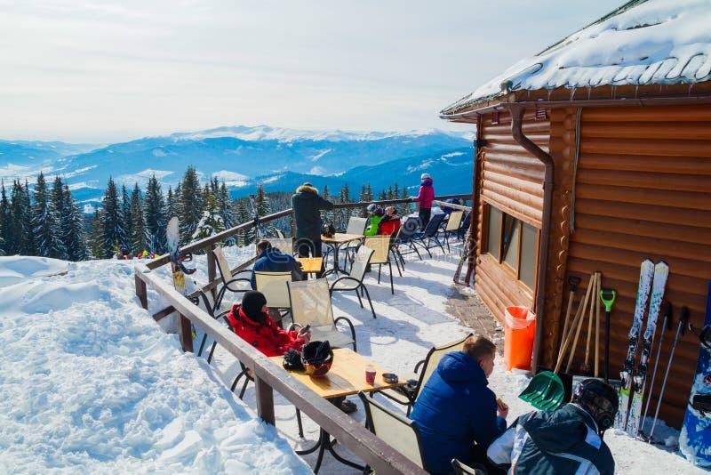 Skifahrer sitzen auf Stühlen nahe einem Restaurant auf einen Berg Leute im Skianzugrest und -getränk lizenzfreies stockbild