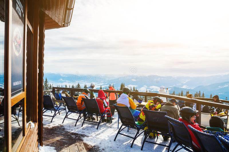 Skifahrer sitzen auf Stühlen nahe einem Restaurant auf einen Berg Leute im Skianzugrest und -getränk stockbilder