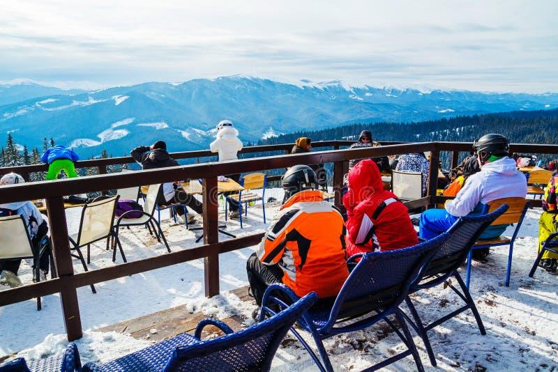 Skifahrer sitzen auf Stühlen nahe einem Restaurant auf einen Berg Leute im Skianzugrest und -getränk stockfotos