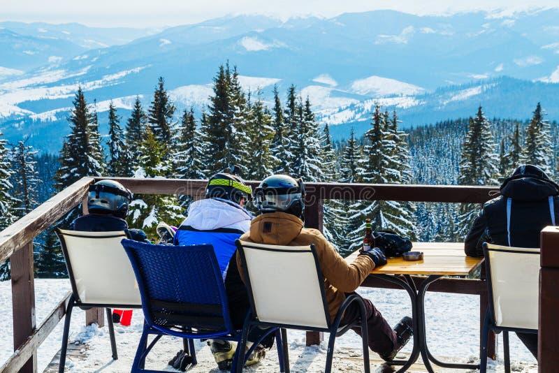 Skifahrer sitzen auf Stühlen nahe einem Restaurant auf einen Berg Leute im Skianzugrest und -getränk stockbild