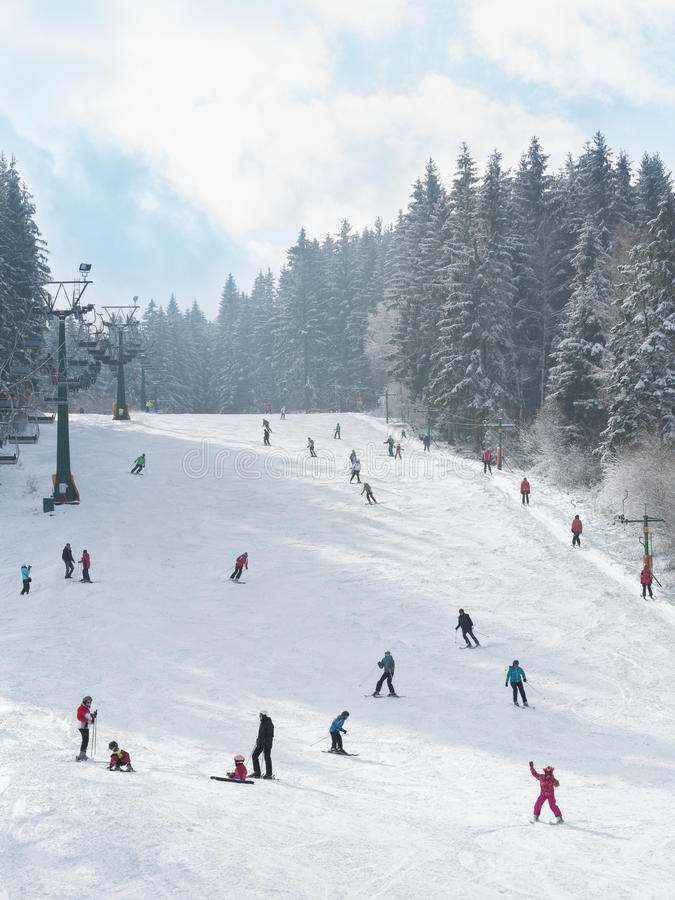 Skifahrer und Snowboarder, die die Steigung hinuntergehen lizenzfreies stockbild