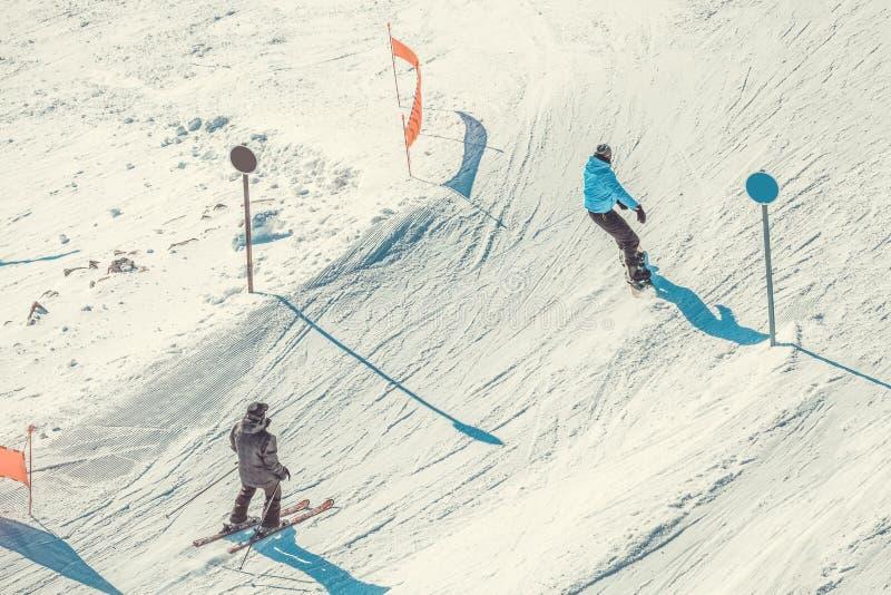 Skifahrer und snownoarder, die abschüssige Fahrt von der Spitze eines Berges tun stockfoto