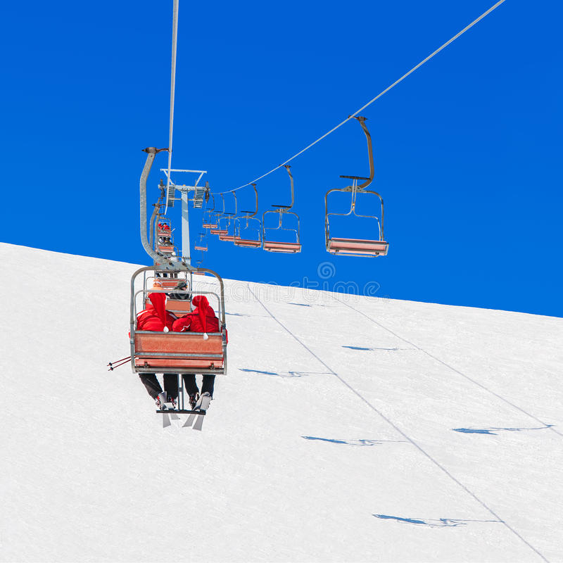 Skifahrer in Weihnachts-Sankt-Hüten am Skifahrenkurortsessellift stockbilder