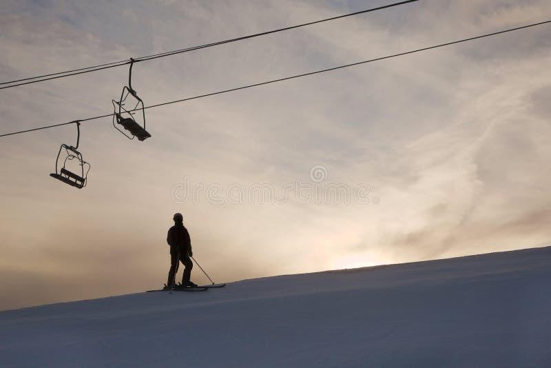 Skifahrerschattenbild gegen glühenden Himmel stockfotografie