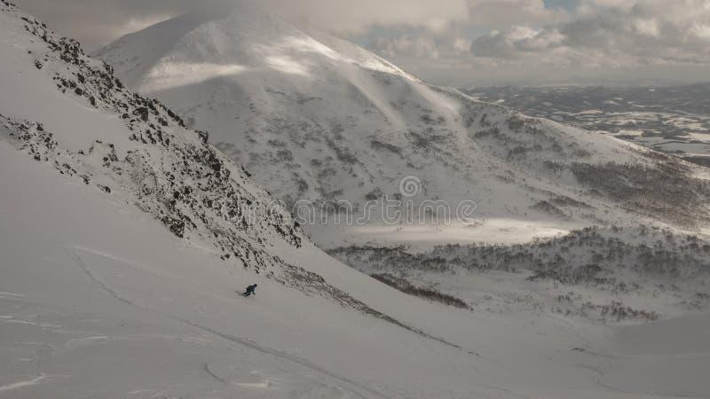 Skifahrerskifahren auf Berg an einem bewölkten Tag stockfoto