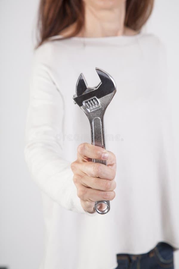 Skiftnyckel i kvinnahand arkivbild