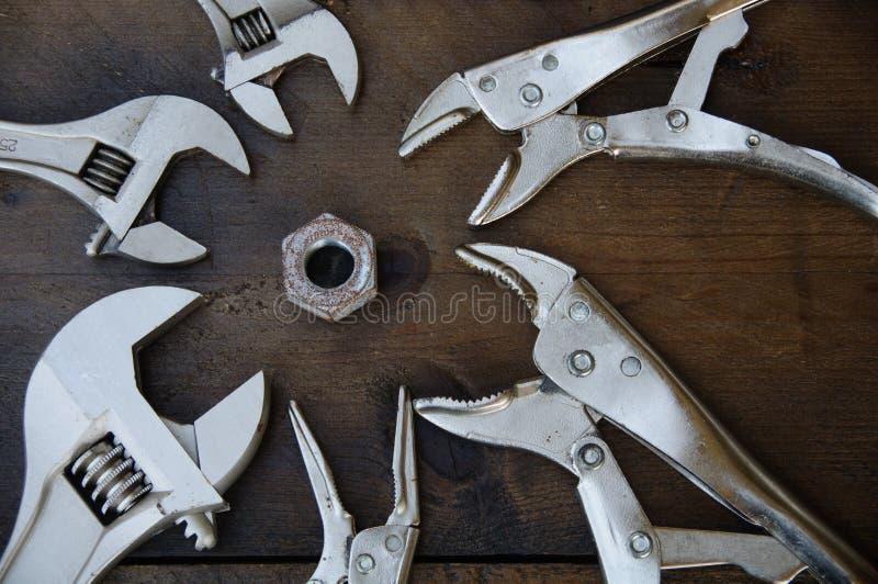 Skiftnyckeln för den justerbara skiftnyckeln eller skruvnyckeloch låsaplattången på träbakgrund, förbereder grundläggande handhjä royaltyfria foton