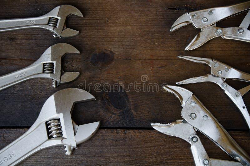 Skiftnyckeln för den justerbara skiftnyckeln eller skruvnyckeloch låsaplattången på träbakgrund, förbereder grundläggande handhjä fotografering för bildbyråer
