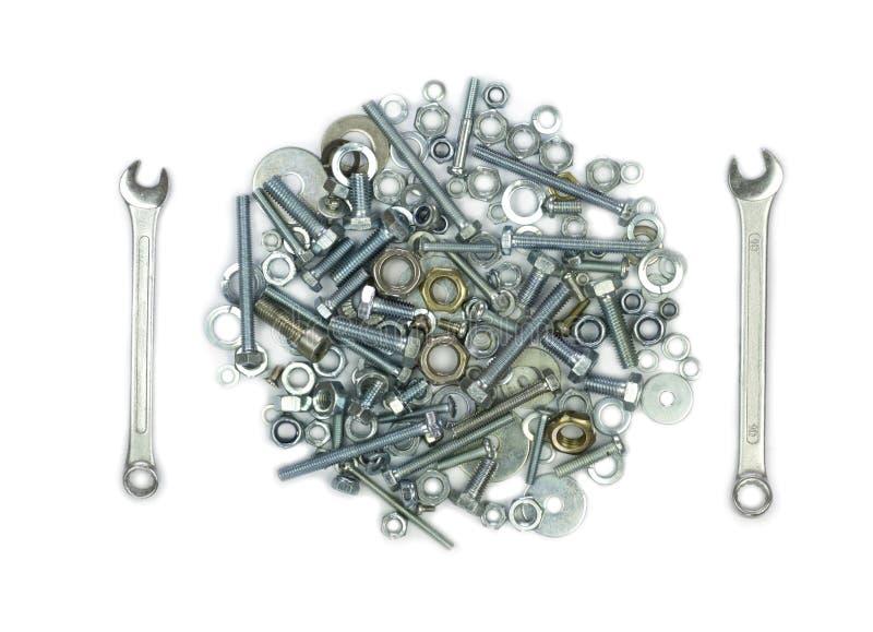 Skiftnycklar, bultar, muttrar, skruvar och packningar Begreppsmässig bild av gaffeln och kniven som ett mål royaltyfria bilder