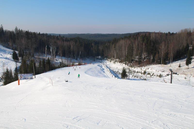 Skihelling, mensen die onderaan de heuvel, bergenmening ski?en Cesis letland royalty-vrije stock afbeelding