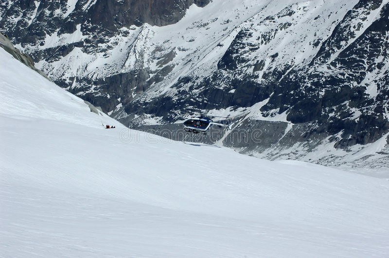 Skiing accident and helicopter recovery stock photography