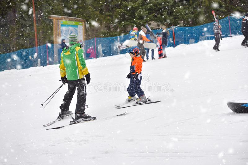 Skiing boy learning from ski teacher, in ski suit and helmet on royalty free stock images