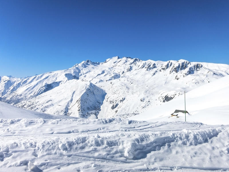 Skiing in French alps with a small hut covered with snow. Les Sybelles ski slopes in France stock photography