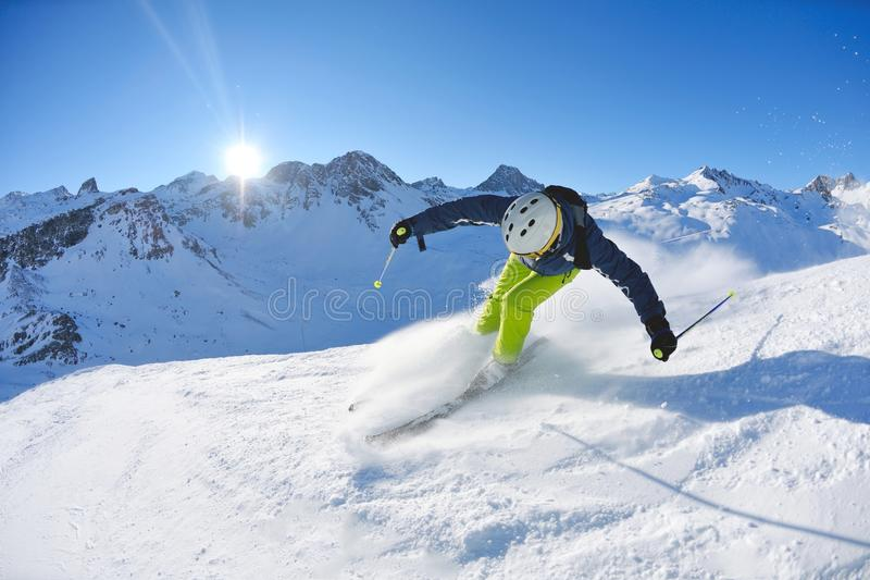 Skiing on fresh snow at winter season at sunny day. Skier skiing downhill on fresh powder snow with sun and mountains in background stock photos