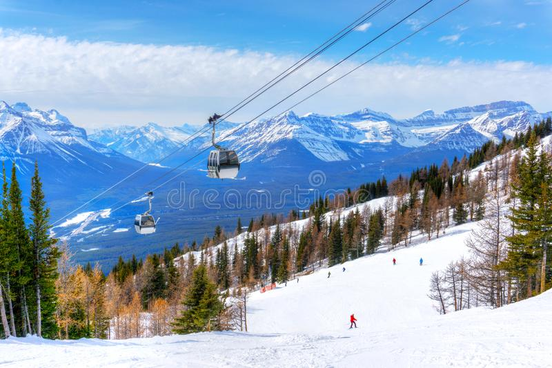 Skiing at Lake Louise in the Canadian Rockies of Alberta, Canada. With cable cars going up the mountains royalty free stock image