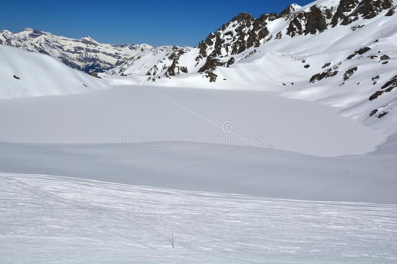 Skiing. Ski tracks cross a frozen lake in the mountains in Switzerland on a beautiful sunny day stock photo