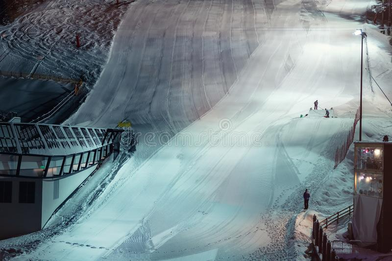Skiing slope downhill prepared for night performance show with artificial lighting in nighttime at austrian alpine resort Ischgl. Activity, maintenance royalty free stock photos