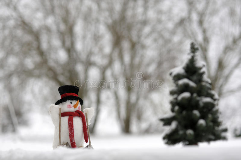 Skiing snowman in winter landscape royalty free stock images