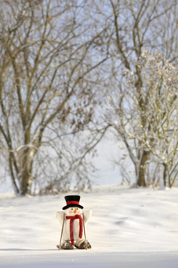 Skiing snowman in winter landscape royalty free stock image