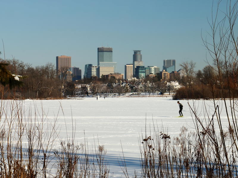 Skiing under the Minneapolis Skyline on Lake of the Isles. The downtown Minneapolis skyline is photographed on a sunny winter day showing a popular winter stock photo