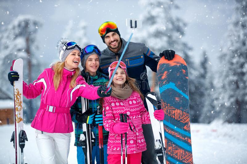 Skiing, winter fun - Mother taking selfie with her family on snow in mountains royalty free stock photos