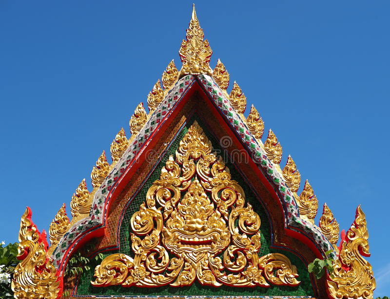 Skilfully crafted gable soaring into blue sky. At Buddhist temple in Thailand stock photo