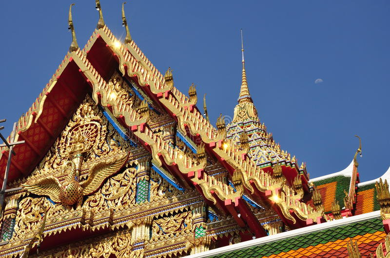 Skilfully crafted gable soars into blue sky. Skilfully crafted gable at Buddhist temple soars into blue sky in Thailand royalty free stock images
