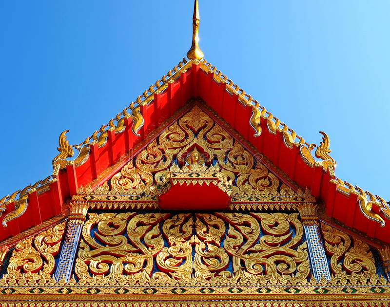 Skilfully crafted gable at Thai temple. Skilfully crafted gable at Buddhist temple soars into blue sky in Thailand royalty free stock photo