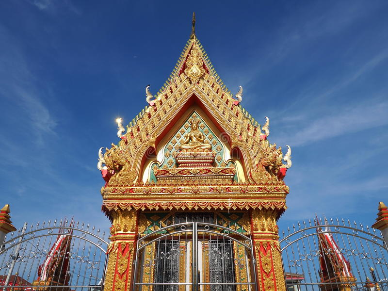 Skilfully crafted Thai temple soars into blue sky. Skilfully crafted gable at Buddhist temple soars into blue sky in Thailand royalty free stock photos