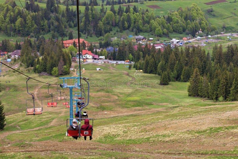 Skilift befördert Leute in das Tal zum Dorf und den Fuß des Berges stockbilder