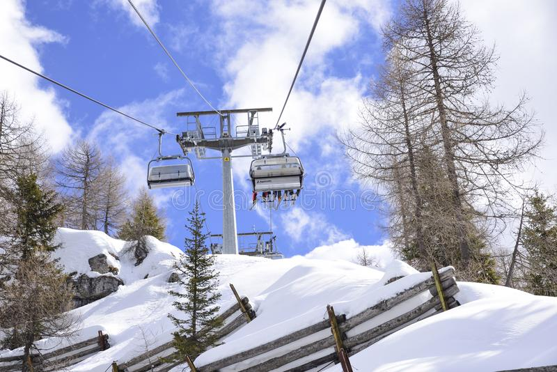 Skilifts towards the ski slopes in the Alps. In the mountains, in the Alps, skiers climb up on the chairlifts to go to the ski slopes royalty free stock photography