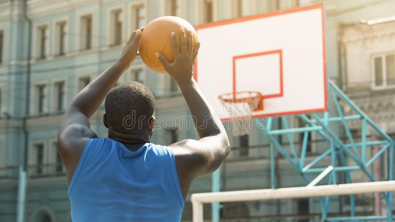 Skilled Afro-American person throwing ball into basket, active sports hobby royalty free stock images
