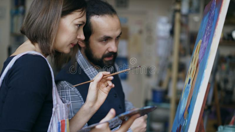 Skilled artist teacher showing and discussing basics of painting to student at art-class. Indoors stock image