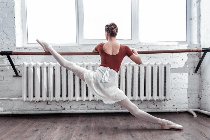 Beautiful nice young woman practicing her splits royalty free stock image