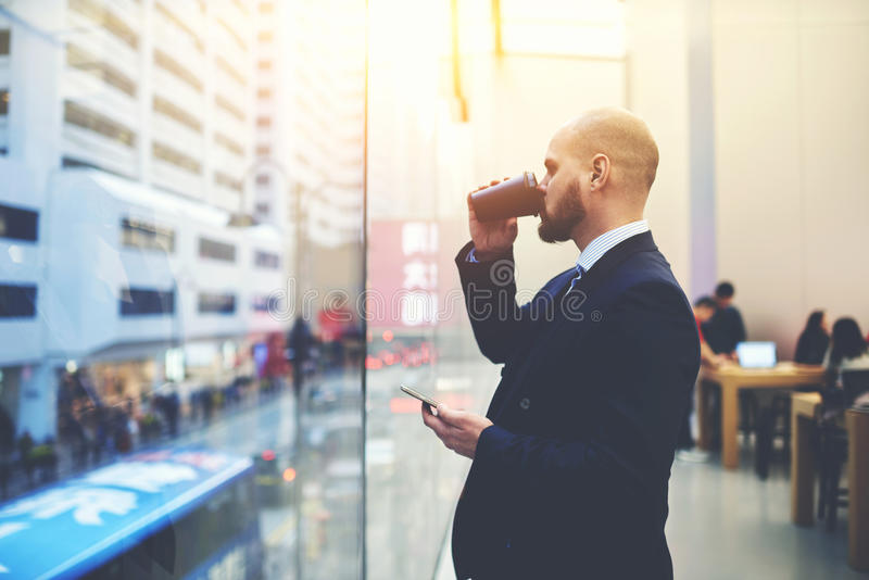 Skilled businessman is watching in window and thinking about his future meeting. Man serious entrepreneur is drinking take away coffee, while is standing with royalty free stock image