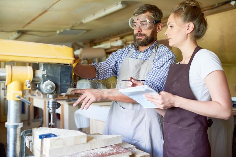 Skilled Carpenter Operating Drilling Machine. Portrait of bearded carpenter explaining operating process of drilling machine to his female assistant in stock images