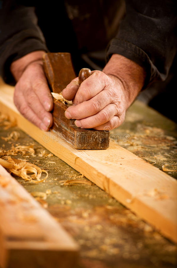 Skilled carpenter using a handheld plane royalty free stock photos