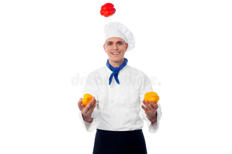 Skilled chef juggling with capsicums royalty free stock photography