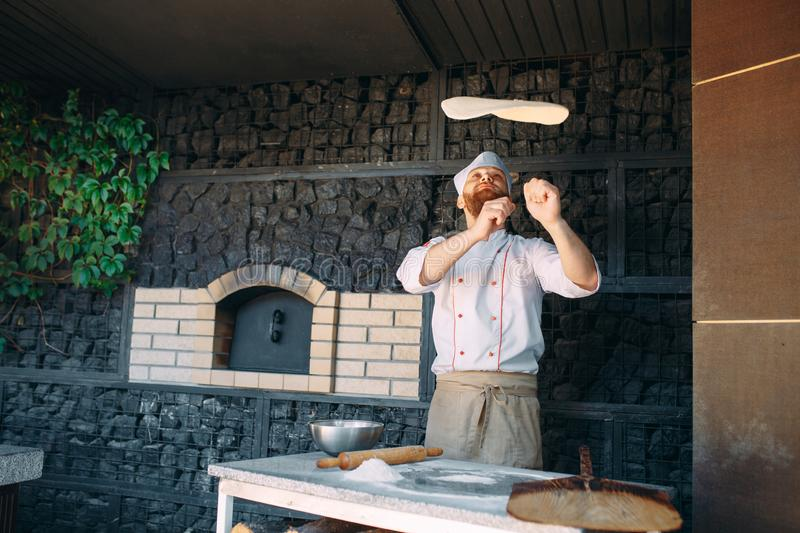 Skilled chef preparing dough for pizza rolling with hands and throwing up. royalty free stock photos
