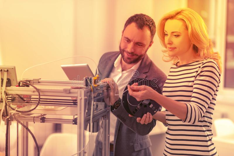 Skilled competent lady and gentleman repairing the damaged 3D printer. royalty free stock photo