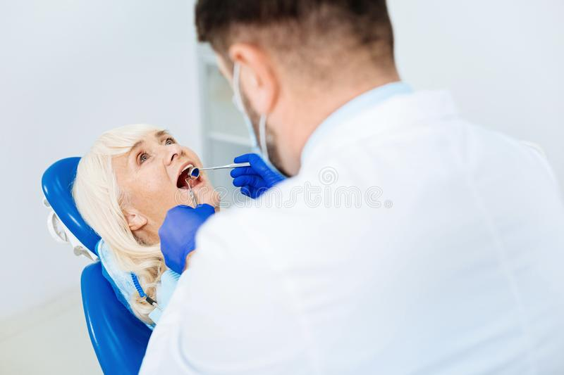 Skilled dentist examining the patient. Working process. Professional dentist using tools while examining patients mouth cavity royalty free stock photos