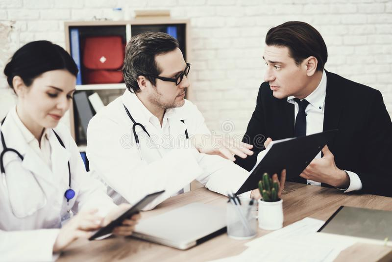 Skilled doctor advises businessman in medical office. Consultation with attending physician. stock image