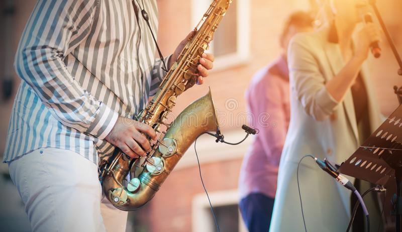 A skilled jazzman plays a saxophone at a concert stock image