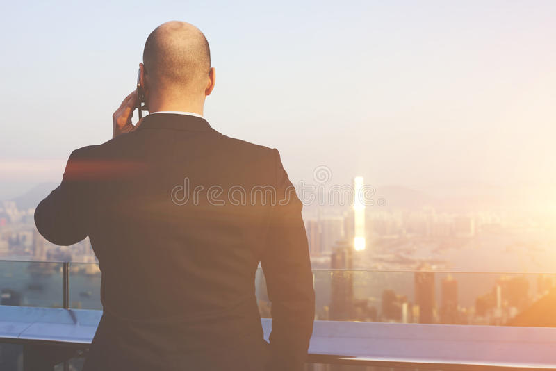 Skilled male CEO is having serious cell telephone conversation during business trip in China royalty free stock image