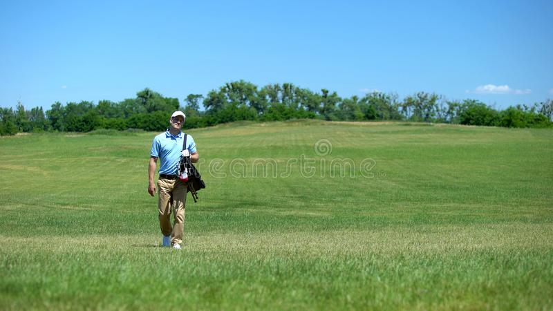 Skilled male golf trainer walking on course with clubs bag recreational activity stock image