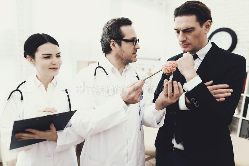 Skilled neurologist shows problem zones on brain model to agitated patient. stock photo