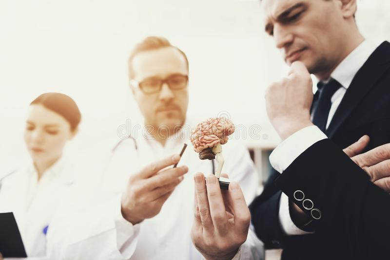 Skilled neurologist shows problem zones on brain model to agitated patient. stock photos