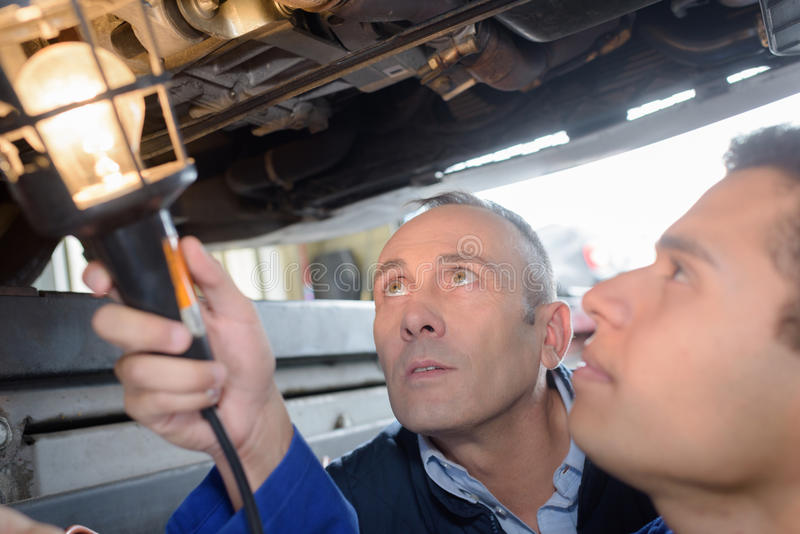 Skilled smiling mechanics working under lifted up car. Skilled smiling mechanics working under a lifted up car stock images