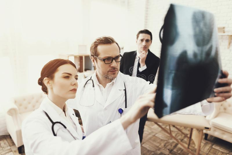 Skilled surgeon and nurse closely study x-ray of pelvic bones of patient. Reception at surgeon. royalty free stock images